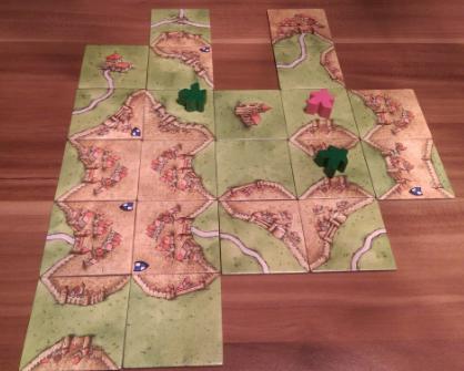 In der Wiese stehen zwei Bauern des einen Spielers und ein Bauer des anderen Spielers. Innerhalb und an der Wiese liegen 3 abgeschlossene und 4 unfertige Städte. Dies ergibt für den Spieler mit zwei Bauern 3*3=9 Punkte